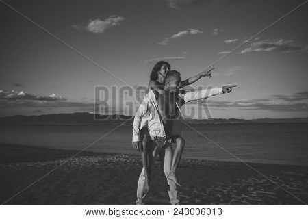 Man Carries Woman In White Dress On Back, Couple Happy On Vacation. Couple In Love Stand On Beach Po
