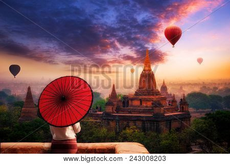 Unidentified Burmese Woman Holding Traditional Red Umbrella And Looks At Hot Air Balloon Over Plain