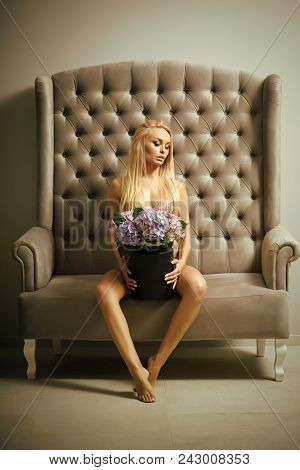 Sensual Woman Body. Sensual Woman With Flowers On Grey Sofa. Sexy Girl With Blond Hair Cover Nude Bo