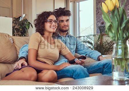 Happy Young Couple Cuddling While Watching Tv In Their Living Room.