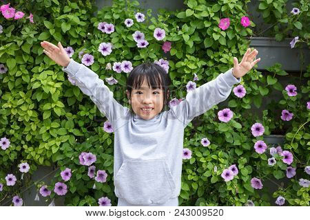Asian Chinese Little Girl Posing Next To Morning Glory Flowers Wall Outdoor