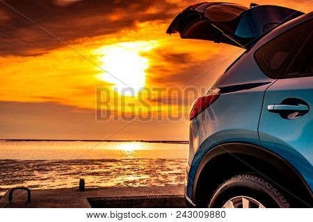 Blue Compact Suv Car With Sport And Modern Design Parked On Concrete Road By The Sea At Sunset. Envi