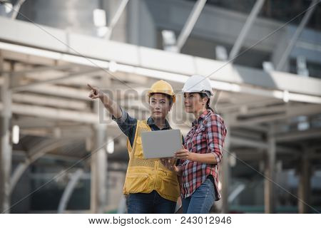 Asian Engineers Group Consult Construction On Site Building Working While Holding Laptop Computer An