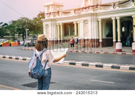 Young Asian Woman Traveler With Backpack And Hat Standing And Looking For Search Way For Travel At T