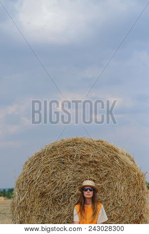 A Woman In A Straw Hat Resting Near A Haystack