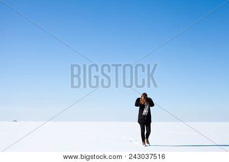 Teenage Girl Walks Along The Endless Snowfield Under Bright Blue Winter Sky