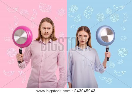 Serious People. Confident Serious Cooks Frowning And Holding Colorful Frying Pans