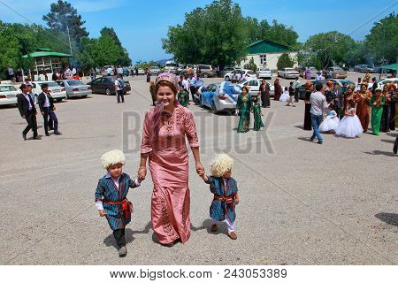 Kov-ata, Turkmenistan - April 30, 2017: Mother With Two Children Dressed In National Clothes. Turkme