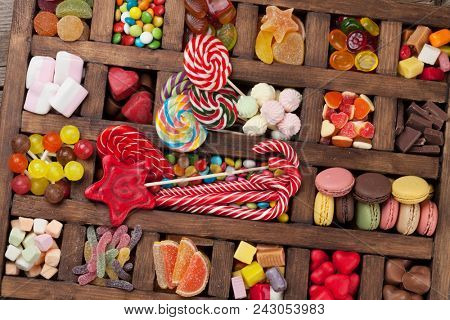 Colorful sweets box. Lollipops, macaroons, marshmallow, marmalade and candies. Top view