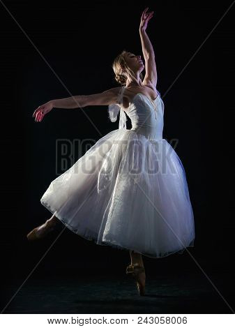 Graceful Ballerina In White Tutu Dress Dancing Elements Of Classical Or Modern Ballet In The Dark Wi