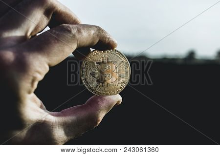 Miner Holds Bitcoin At Dawn. Bitcoin In Dirty Hands. One Bitcoin In The Hands