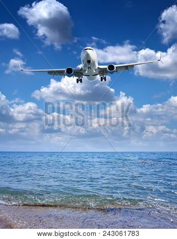 Passenger Airplane Prepare For Landing On Sunny Mediterranean Sea And Sky Background