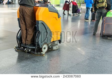 Man Driving Professional Floor Cleaning Machine At Airport Or Railway Station.  Floor Care And Clean
