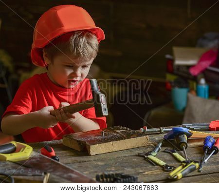 Child In Helmet Cute Playing As Builder Or Repairer, Repairing Or Handcrafting. Toddler On Busy Face