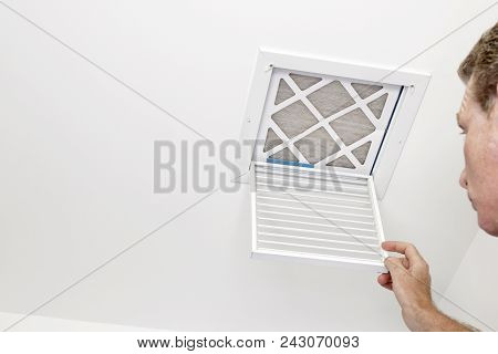 Mature adult opening a small square HVAC air intake vent revealing a dirty air filter in the ceiling. Man opened a a vent grill cover to a dirty ceiling air filter. poster