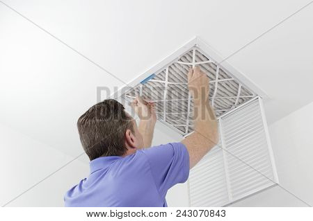 Caucasian Male Removing A Square Pleated Dirty Air Filter With Both Hands From A Ceiling Air Duct. G