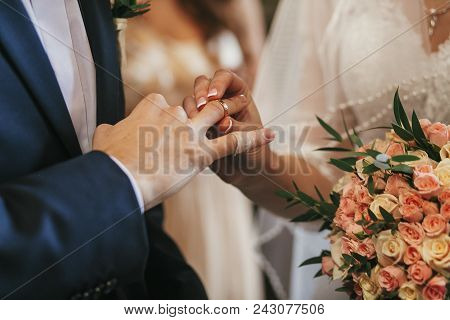 Beautiful Bride And Groom Hands Exchanging Wedding Rings In Church During Wedding Ceremony. Spiritua