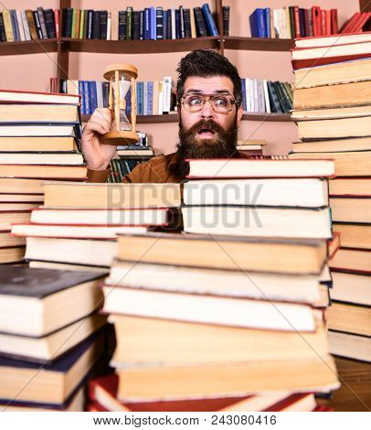 Man On Surprised Face Holds Hourglass While Studying, Bookshelves On Background. Time Flow Concept.