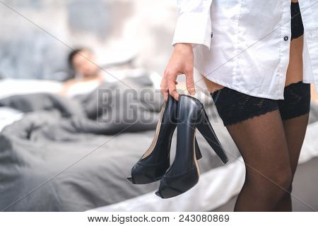 Close Up Of Womans Hand Holding Shoes. Sexy Girl In Underwear Leaves Bedroom After Sex. Sex Concept
