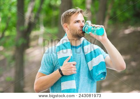 Man With Athletic Appearance Holds Bottle With Water. Sport And Healthy Lifestyle Concept. Athlete D