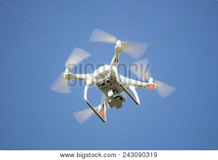 White drone with digital camera, filming from above. Proper for aerial surveillance. Clear blue sky background.