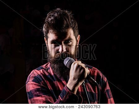 Musician, Singer Makes Effort To Win Musical Contest. Man With Tense Face Holds Microphone, Singing