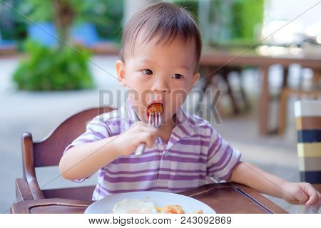 Cute Little Asian 18 Months / 1 Year Old Toddler Boy Child Sitting In High Chair Using Fork Eating W