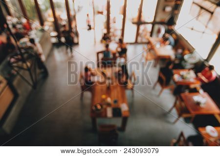Blurred Background Of Cafe, Made In Loft Style With Bid Windows And Wooden Table.