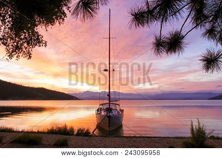 Silhouette Of A Yacht With A Lowered Ladder On Lake Baikal At Dawn. The Concept Of Ecological Travel