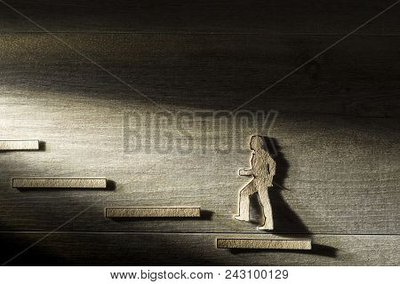 Cut Outs Of Paper Man Walking Up Steps Towards The Light In A Conceptual Image Of Business Success.