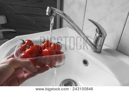 Washing Cherry Tomatoes Under The Tap. Focus Is Where Hand Holds A Box With Tomatoes Under The Tap D