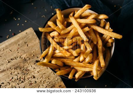 high angle shot of some appetizing french fries served in a white ceramic bowl, placed on a dark gray rustic wooden table