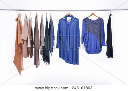 Hangers with colorful clothes on white background