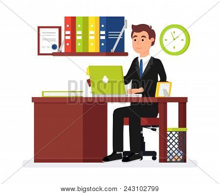 Man Office Worker. Businessman Working Behind Laptop, On Table Are Folder With Papers And Picture In