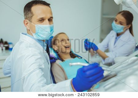 Need It. Charming Assistant Wearing Face Mask While Helping Her Practitioner