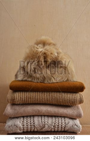 knitted Hat with Stack of knitted sweaters-gray background