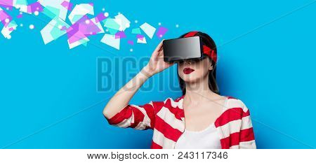 Portrait Of Beautiful Young Woman With Virtual Reality Gadget On Blue Background