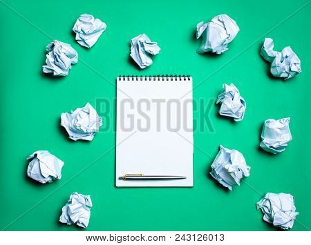White Notebook With Pen On A Green Background Among Paper Balls. The Concept Of Generating Ideas, In