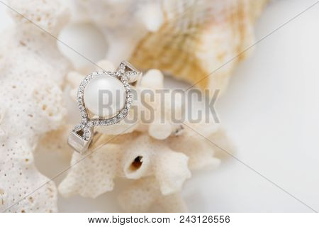 Elegant Silver Ring With Pearl And Diamonds On Coral Against White Background. Summer Jewelry