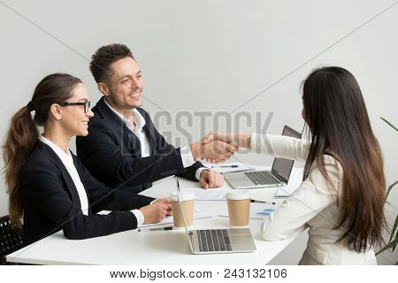 Friendly Satisfied Partners Handshaking At Group Meeting Thanking For Successful Teamwork, Smiling M