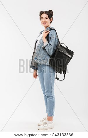 Full length photo of beautiful teenage girl 20s with double buns hairstyle wearing jeans clothing and backpack smiling at camera isolated over white background poster