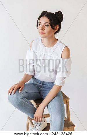 Portrait closeup of thoughful teenage girl 20s with double buns hairstyle looking aside with brooding glance while sitting in chair isolated over white background
