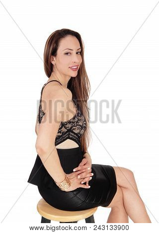 A Beautiful Young Woman Sitting On A Chair In A Black Leather Skirt And Long Brunette Hair, Smiling,