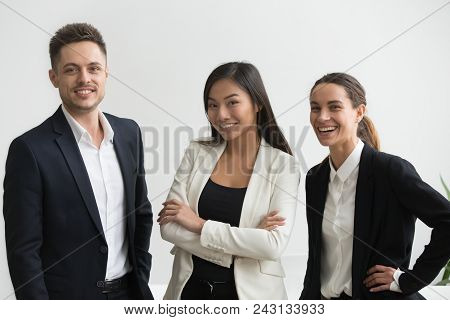 Millennial Smiling Multi-ethnic Professional Office Employees Looking At Camera, Asian And Caucasian