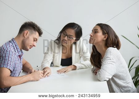 Unhappy Married Family Couple Getting Divorced In Asian Attorney Lawyers Office, Husband Signing Dec
