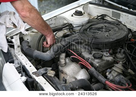 Checking the oil dip stick on car