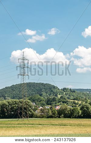 Power Pylon In The German Countryside With Forests, Fields And Meadows