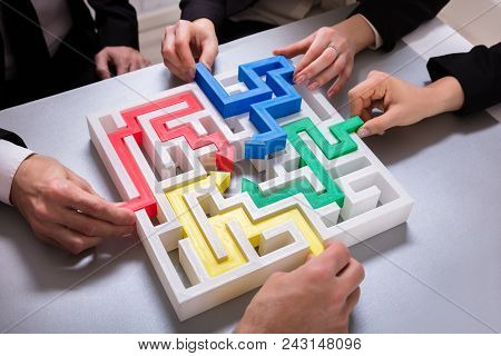 Elevated View Of Businesspeople Hand Solving Maze Puzzle On Desk In Office