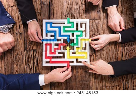 Elevated View Of Businesspeople Hand Solving Maze Together On Wooden Background