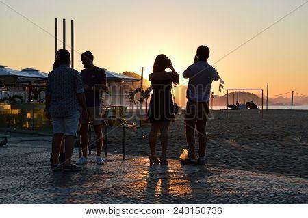 Rio De Janeiro, Brazil - May 27, 2018:  Tourists Take Photos Of Sunrise On Copacabana Beach